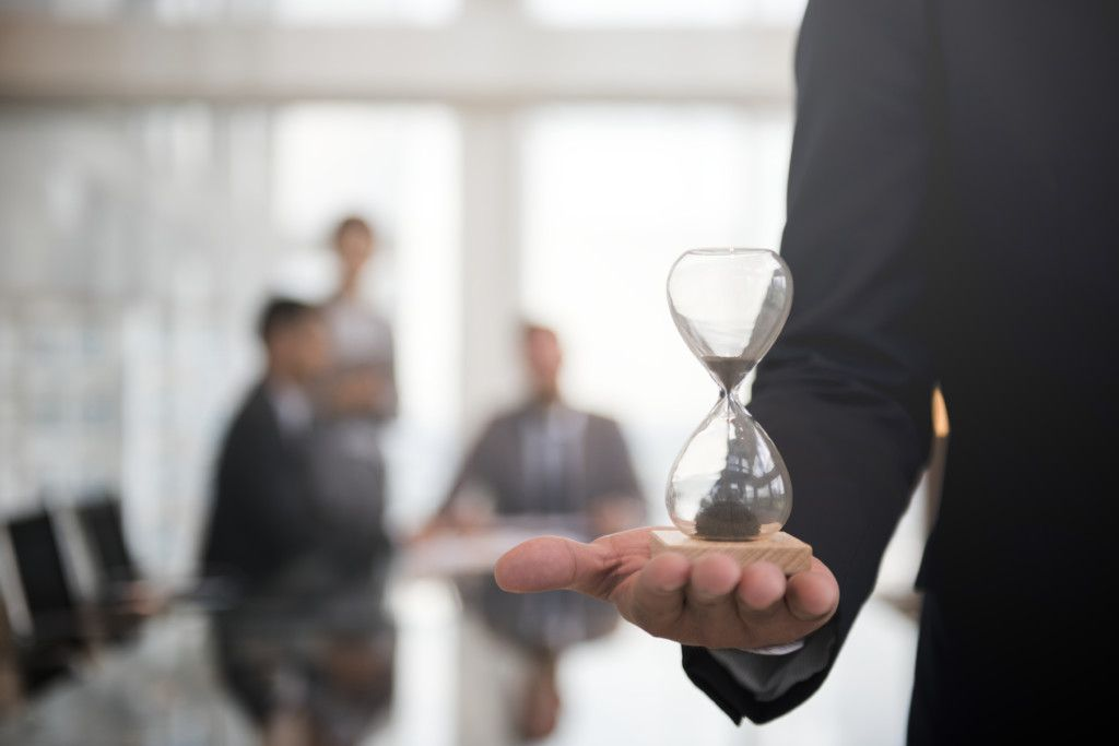 Businessman holding an hour glass,getting passive income freenancial exposed